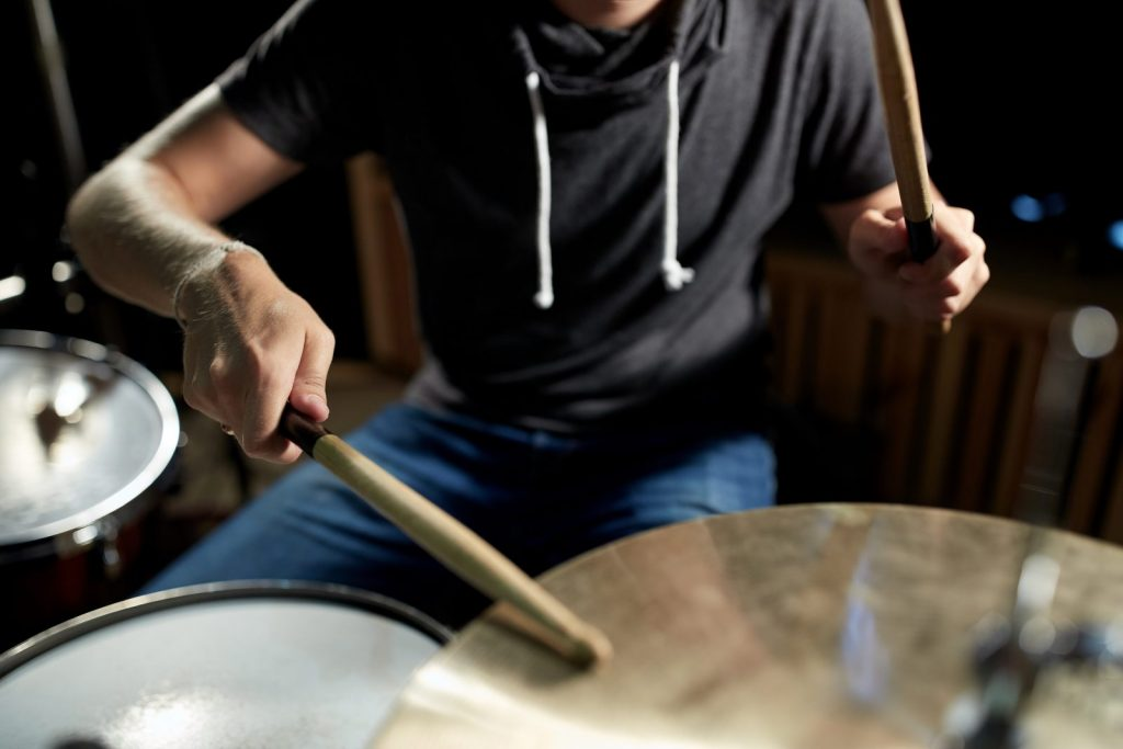 male-musician-playing-drums-and-cymbals-at-concert-PE5VJN6